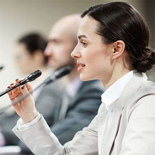 a woman speaking into a mic at a conference
